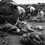 01 May 1961, Naples, Italy --- Original caption: 5/1/1961-Naples, Italy - Archaelogical workers extract the mummified bodies of two adults and three children from earthen mold here May 1st. These bodies are victims of an eruption which buried the ancient city of Pompeii in the year 79 A.D., when Mt. Vesuvius erupted. --- Image by © Bettmann/CORBIS